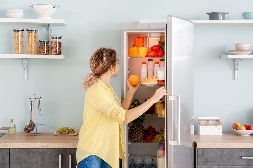 Fiatal lány gyümölcsöt vesz ki a hűtőből